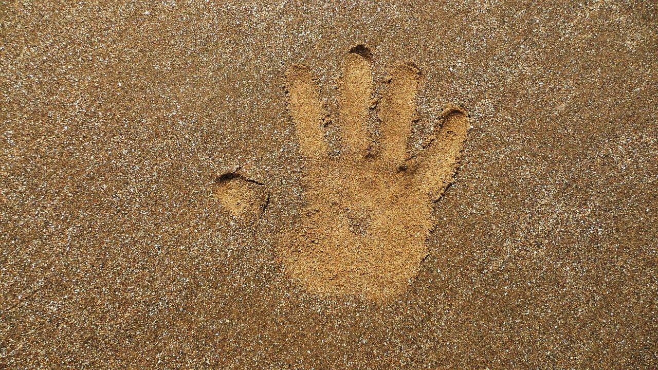 Abruck einer Hand in hellem Sandstrand