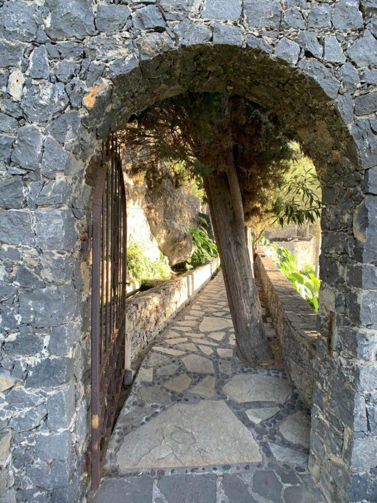 Eingang durch eines Steinmauer mit einem Eisentor; Foto: Roland Strobl
