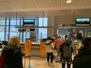 Passagiere stehen vor einem Flugschalter bereit ins Flugzeug einzusteigen