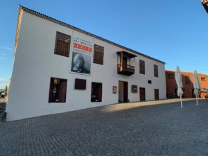 Das Museum MACEW in Puerto de la Cruz von der Seite aus. Weiße Hauswand mit Fenstern und Ausstellungsplakat
