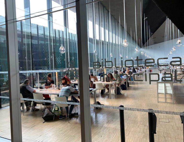 Blick durch eine Glaswand in die Bibliothek