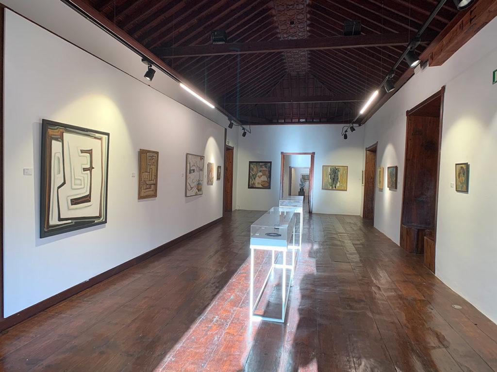 Ausstellungsraum mit Bildern an der Wand und einer Glasvitrine und einem Exponat.