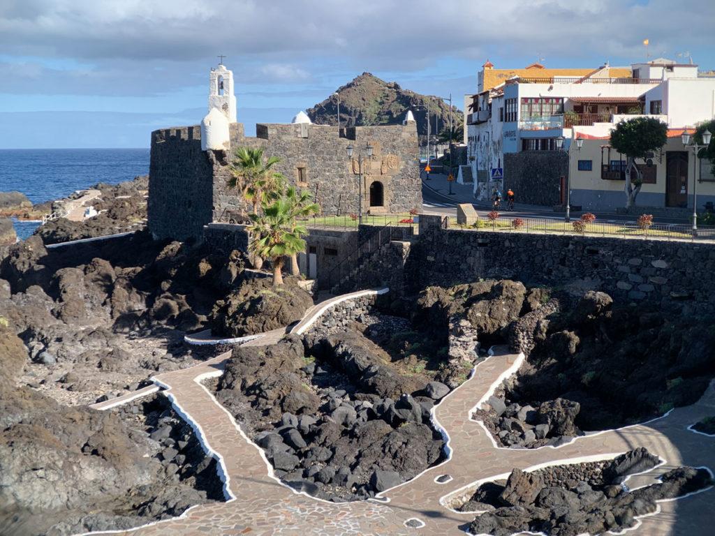 Ein mittelalterliches Hafenkastell aus Steinen mit weissem Turm. Unterhalb davon rötliche Steinwege mit weißen Rändern