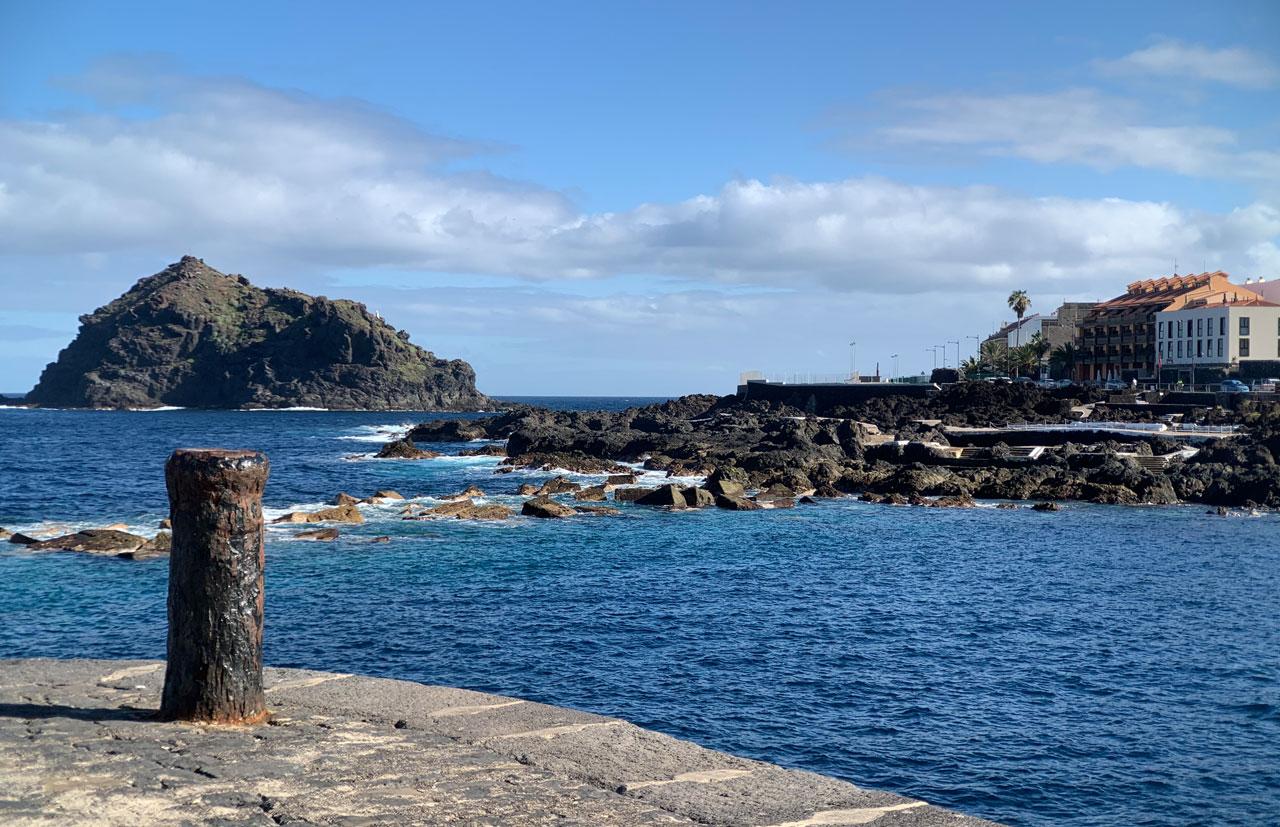 Im Vordergrund steht ein eiserne Pfahl auf der Mole. Im Hintergrund schwere Lavainsel im blauen Meer