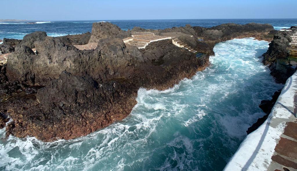 Ein Naturpool mit tosendem Wasser der von Lavafelsen vom offenen Meer getrennt ist.