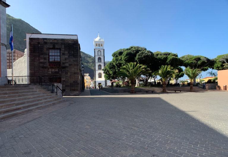 Großer Steingepflasterter Platz vor der Plaza de la Libertad in Garachico mit Blick auf Kirche und Freiheitsplatz unter indischem Lorbeer