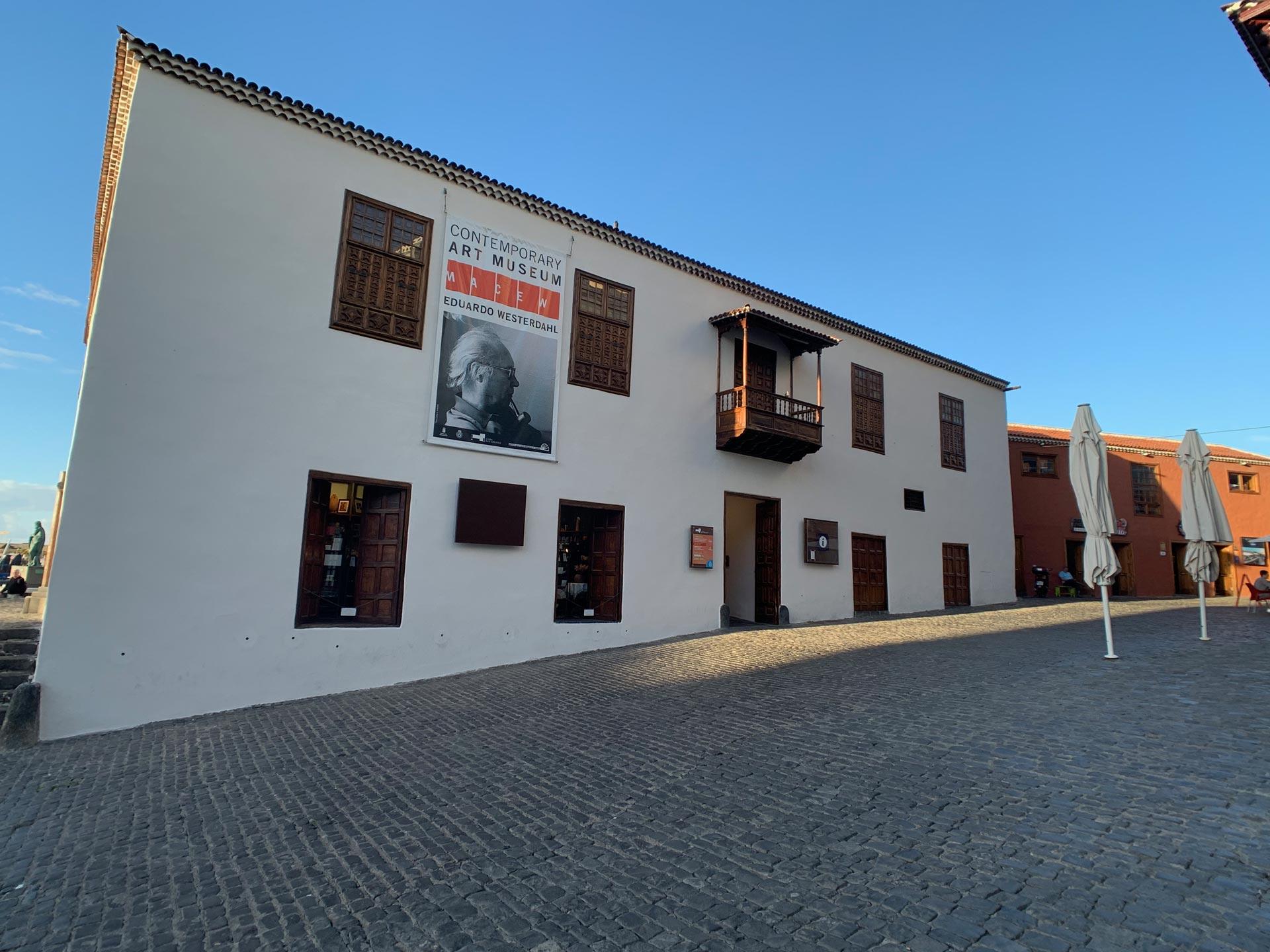Weisse Hausfassade des Museums mit Holzfenstern und einem Ausstellungsplakat