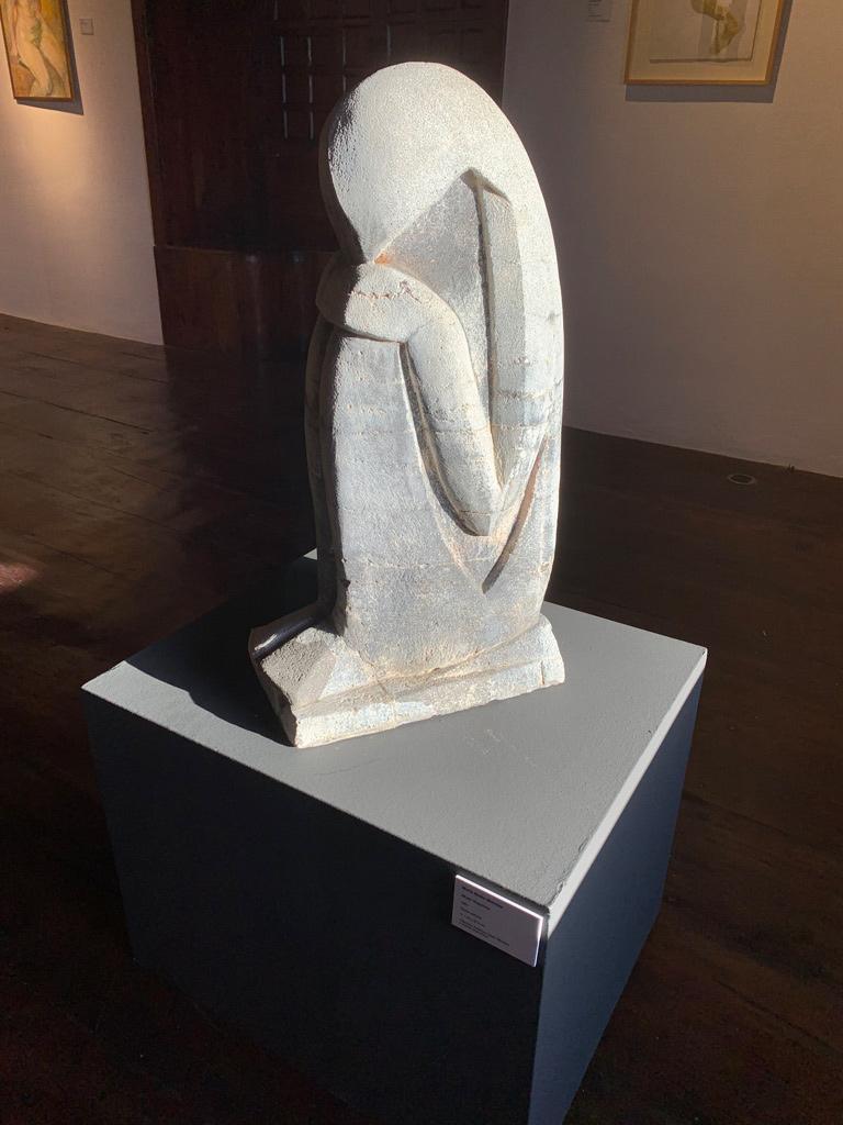 Steinskulptur eines kauernden Menschen