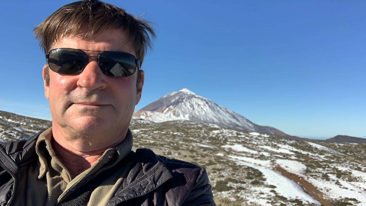 Selfie eines Mann mit dunkler Sonnenbrille. Im Hintergrund sieht man den Teide mit Schnee