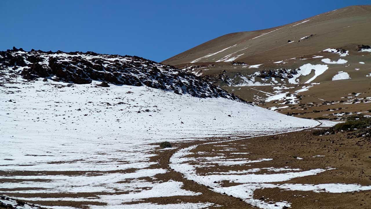 Schneebedeckter Wanderweg auf dem Teide. Rechts oben Montana Rajada mit blauem Himmel