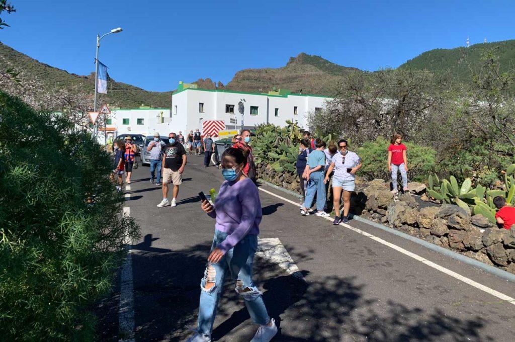 Mehrere Menschen mit Mundschutzmasken stehen und gehen auf kleiner Straße vor einem Dorf.