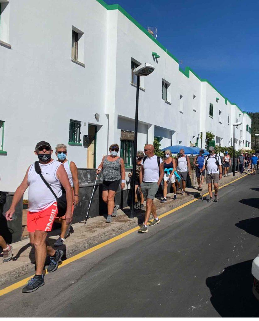 Menschen in sommerlicher Kleidung, kurzen Hosen laufen auf einer kleinen Strasse hintereinander. Sie tragen Mundschutzmasken wegen CoVid.