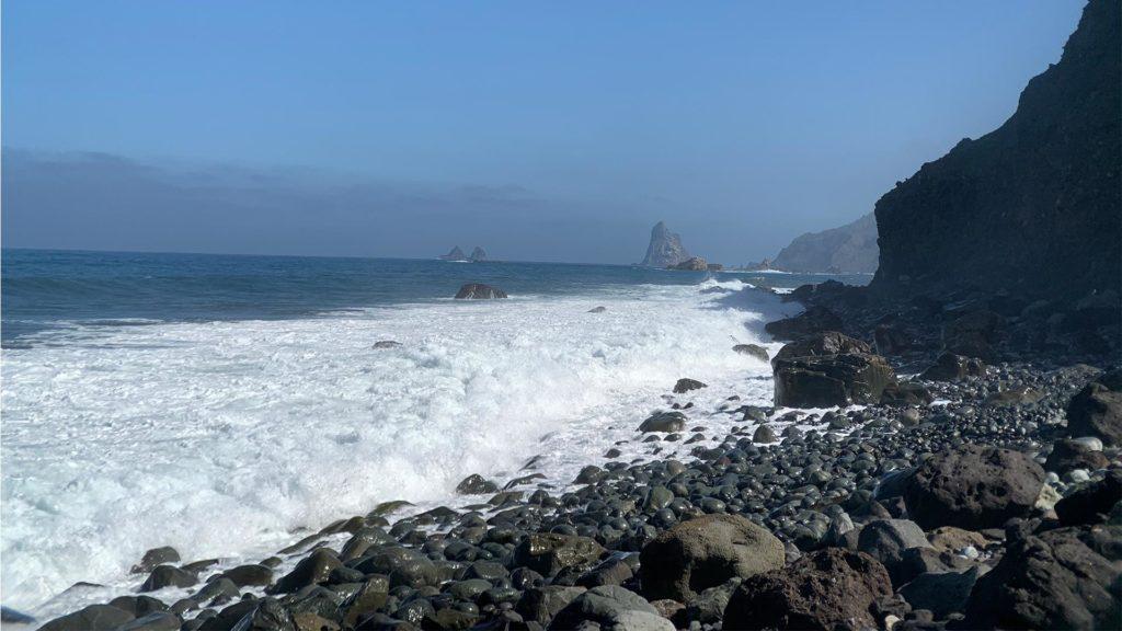 Der Küstenabschnitt El Cardonal mit großen Lavasteinen, Meereswellen und der Felsformation Las Baja im Hintergrund