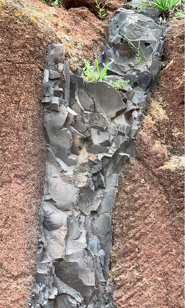 Eine rote Lavasteinwand in der sich der Einschluss einer anderen Gesteinsschicht befindet