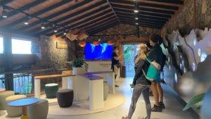 Innenraum des Besucherzentrums von Masca. Besucher stehen vor dem Parkverwalter
